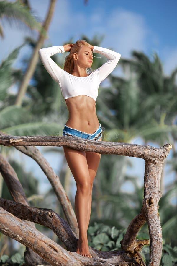 Donna che posa sulla spiaggia tropicale vicino alle palme fotografia stock