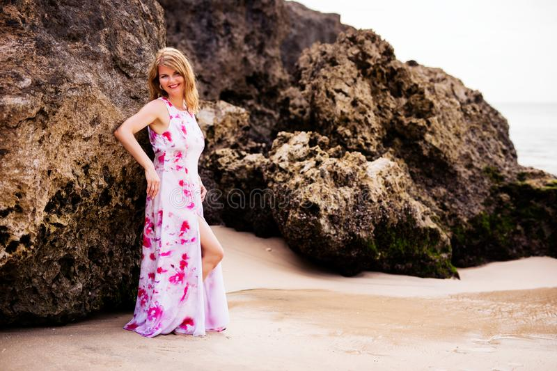 Donna che posa sulle rocce della spiaggia fotografia stock libera da diritti