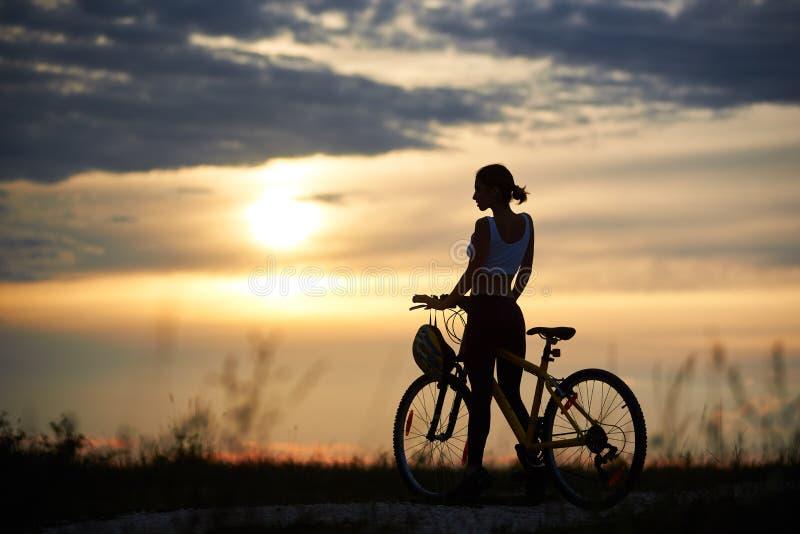 Donna che posa vicino alla bici ed alla natura enoying immagini stock