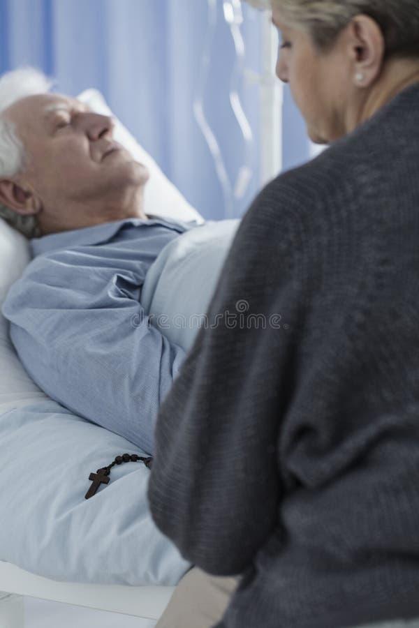Donna che prega all'ospedale fotografie stock libere da diritti
