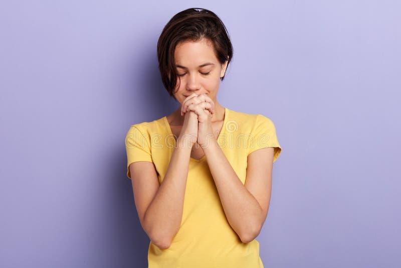Donna che prega con gli occhi chiusi Le sue mani sono incatenate dalle manette fotografia stock