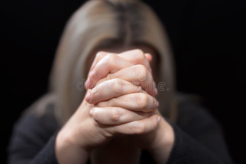 Donna che prega con le sue mani afferrate davanti al suo fronte immagini stock libere da diritti