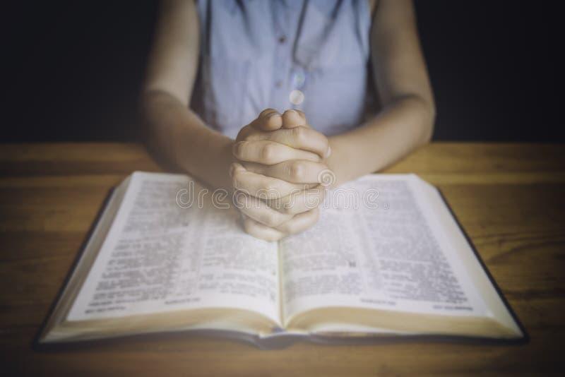 Donna che prega con le sue mani su bibbia immagine stock
