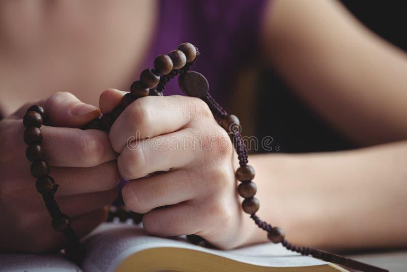 Donna che prega con le sue perle del rosario e della bibbia immagini stock
