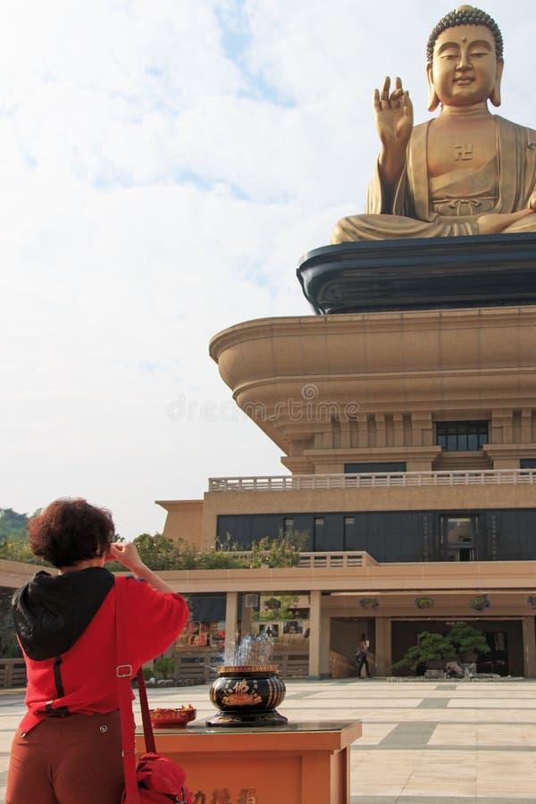 Donna che prega il Buddha gigante e l'incenso bruciante alle FO Guang Shan di Taiwan, Kaohiung immagine stock libera da diritti