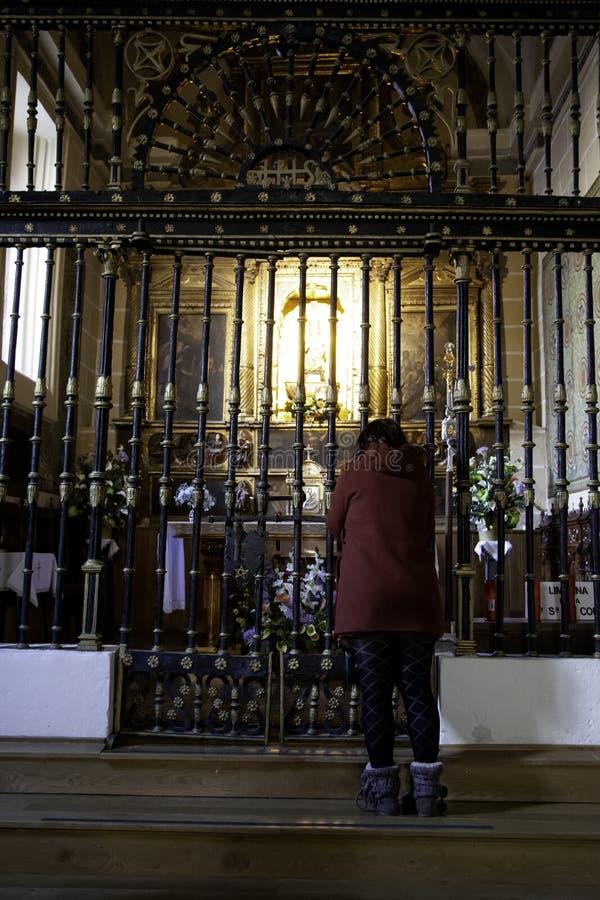 Donna che prega nella chiesa fotografie stock