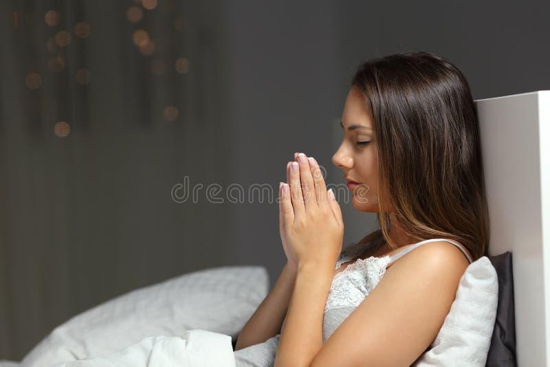 Donna che prega nella notte in un letto a casa immagini stock libere da diritti