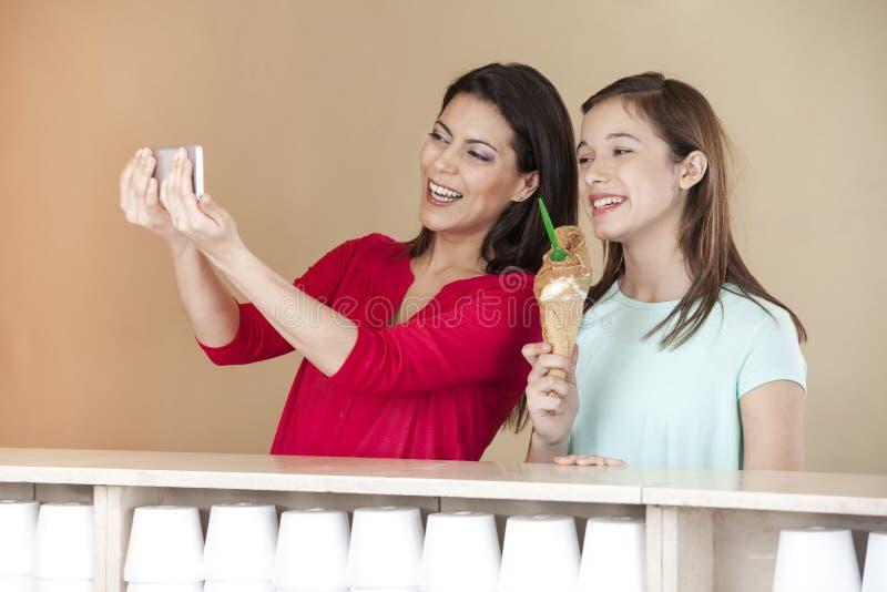 Donna che prende autoritratto con il ghiaccio del cioccolato della tenuta della figlia immagini stock