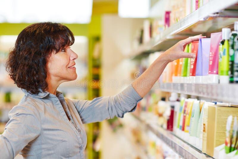 Donna che prende decisione di acquisto in farmacia fotografie stock