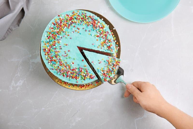Donna che prende fetta di torta di compleanno deliziosa fresca alla tavola fotografie stock