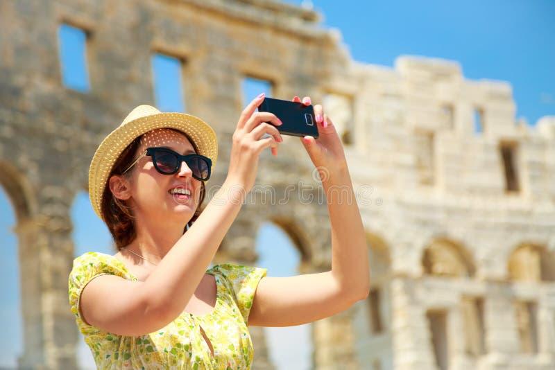 Donna che prende foto dell'arena con Smartphone immagini stock libere da diritti