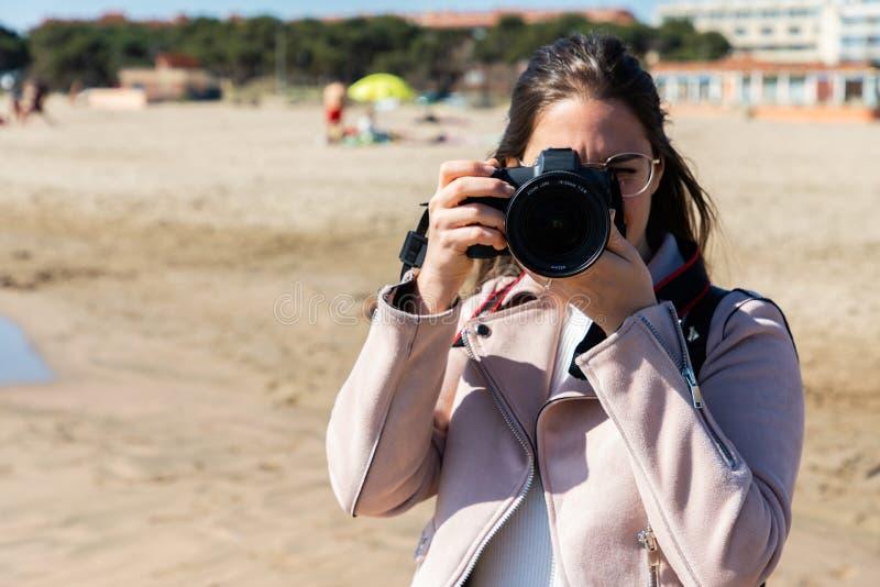 Donna che prende a foto vista frontale con la macchina fotografica di DSLR fotografia stock