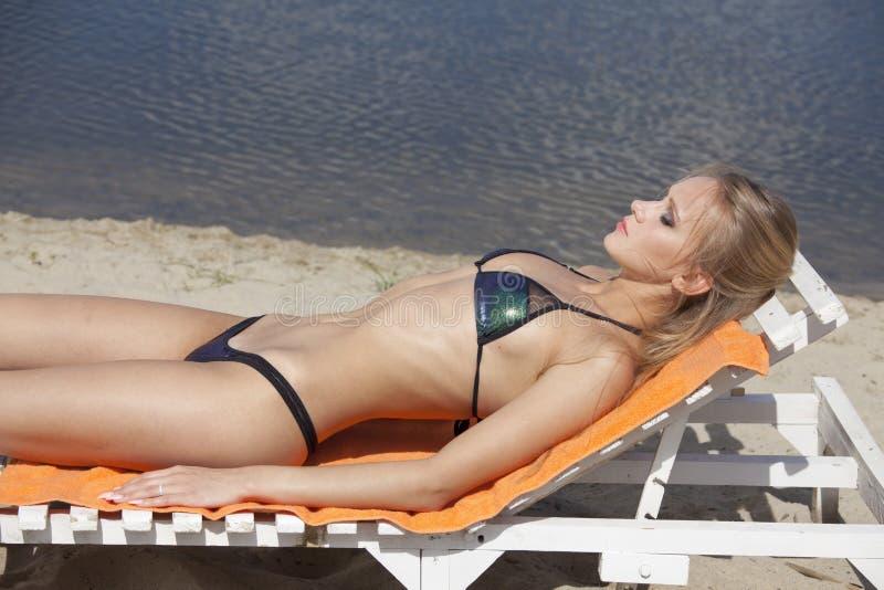 Donna che prende il sole sulla sedia fotografia stock libera da diritti