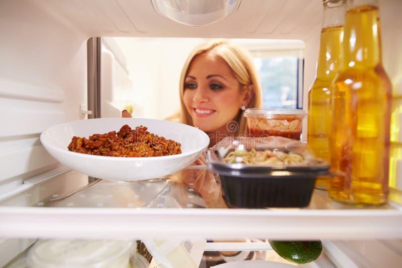 Donna che prende piatto di alimento rimanente dal ½ del ¿ di Fridgeï fotografie stock libere da diritti