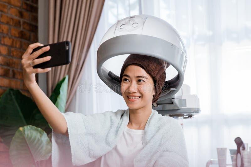 Donna che prende selfie mentre ottenendo trattamento fotografie stock