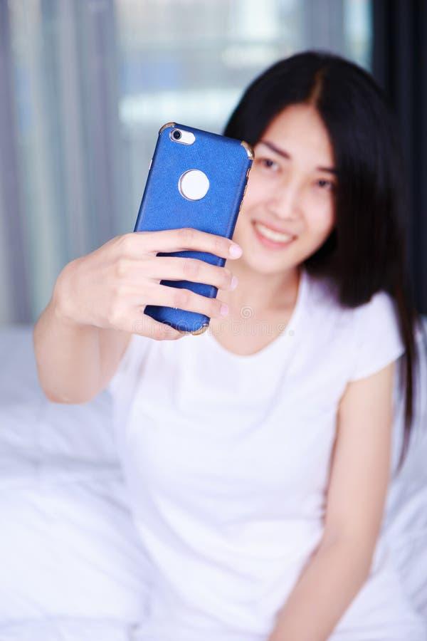 Donna che prende selfie sul letto in camera da letto immagine stock libera da diritti
