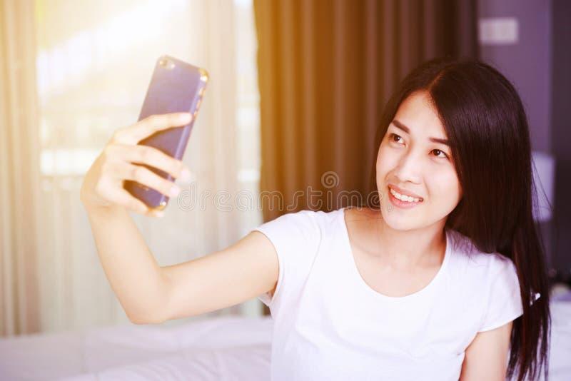 Donna che prende selfie sul letto in camera da letto fotografie stock libere da diritti