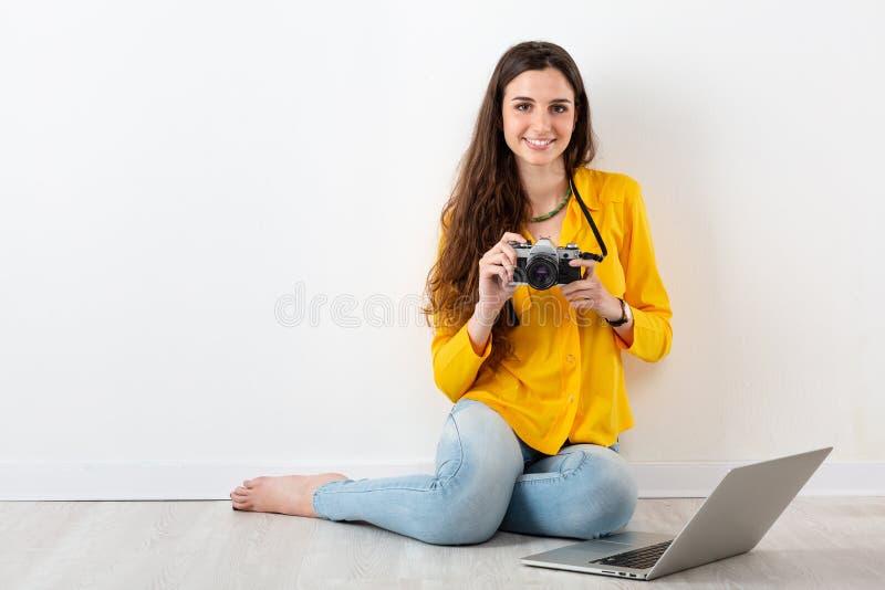Donna che prende un'immagine con una macchina fotografica d'annata fotografia stock
