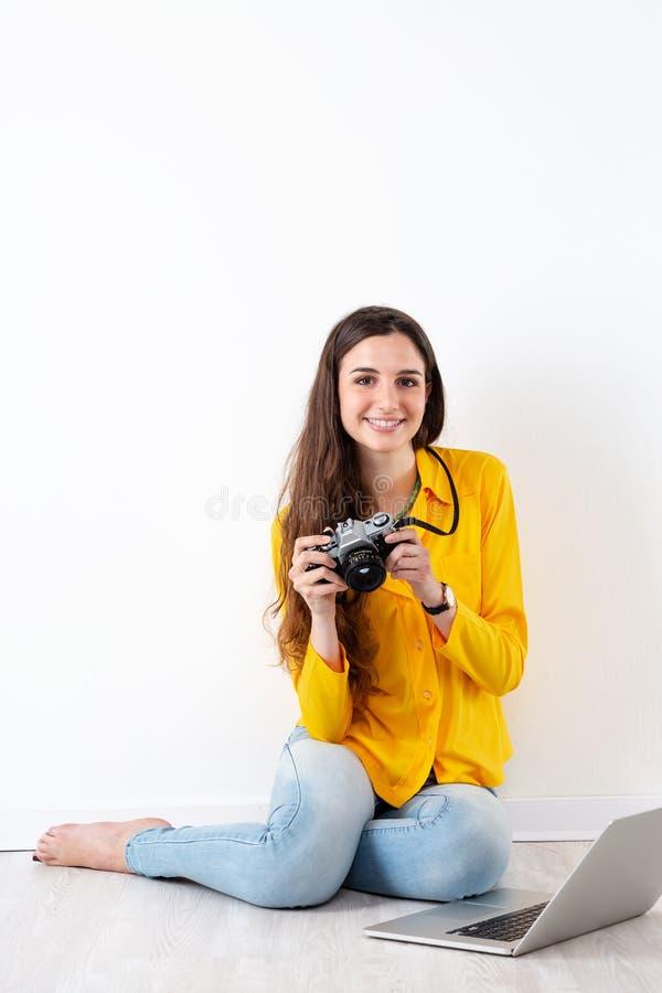 Donna che prende un'immagine con una macchina fotografica d'annata immagine stock