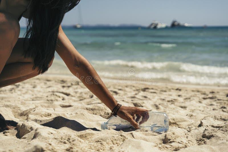 Donna che prende un'immondizia della bottiglia di acqua nella sabbia della spiaggia fotografie stock libere da diritti