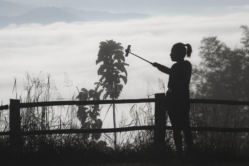 Donna che prende un selfie all'alba sopra un paesaggio nebbioso in norther fotografia stock libera da diritti