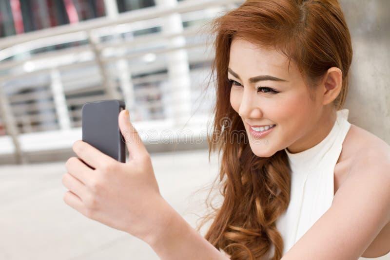 Donna che prende un selfie con il suo smartphone fotografia stock
