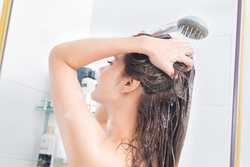 Donna che prende una doccia che gode dell'acqua che spruzza sui suoi capelli Sele fotografia stock