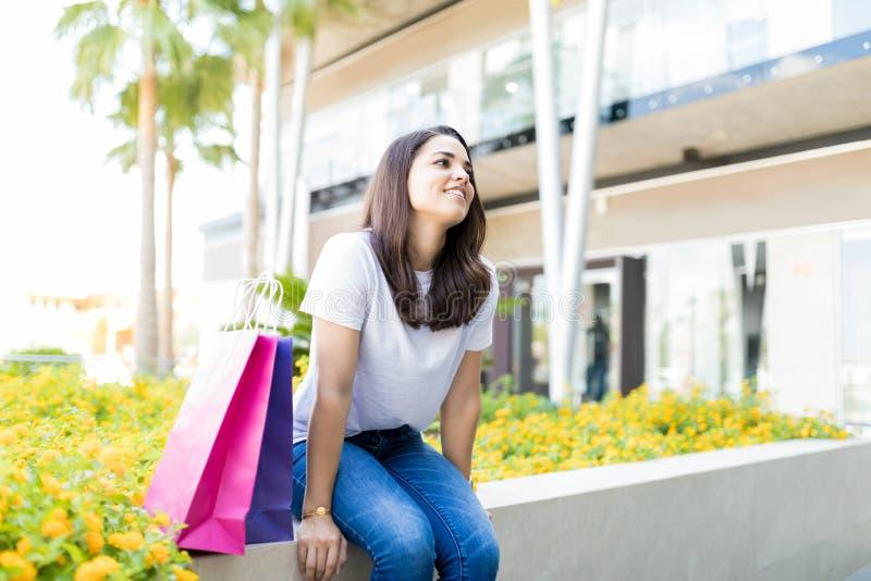 Donna che prende una rottura da acquisto mentre sedendosi fuori del centro commerciale fotografia stock