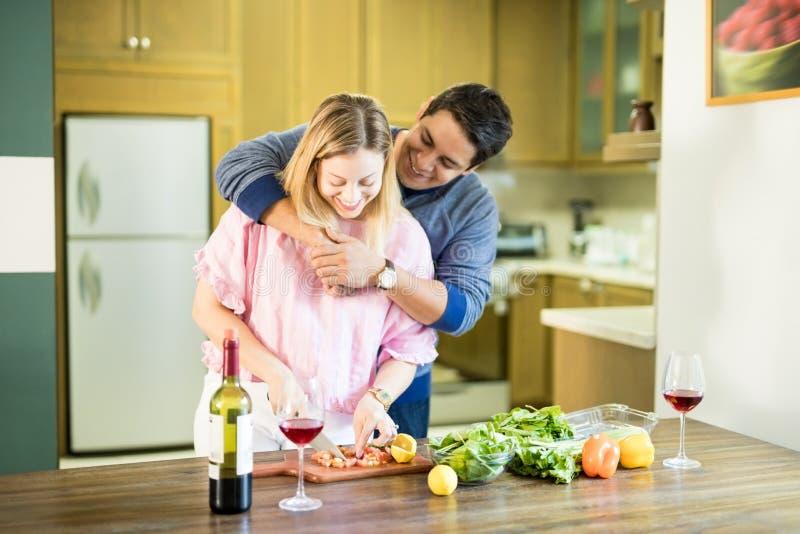 Donna che prepara insalata con il ragazzo in cucina immagine stock libera da diritti