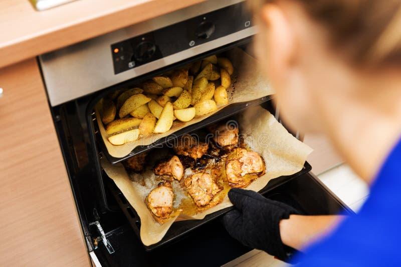Donna che prepara le patate e carne di pollo in forno fotografia stock libera da diritti