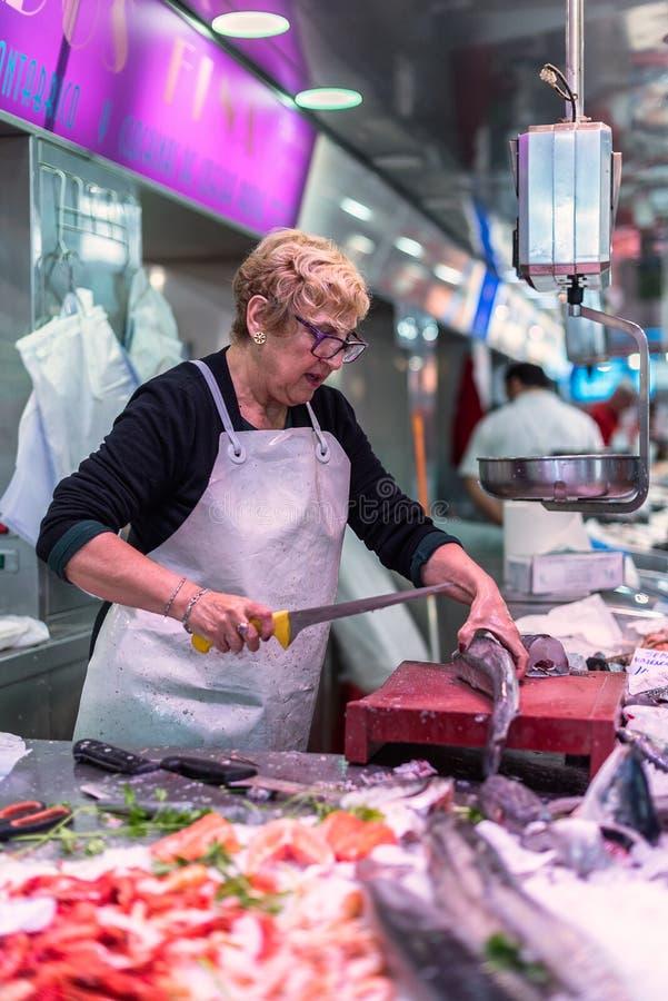 Donna che prepara pesce su una stalla nel mercato centrale del ` centrale di Mercado del ` di Valencia fotografia stock libera da diritti