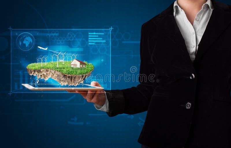 Donna che presenta una terra perfetta di ecologia con una casa e un windmil immagini stock