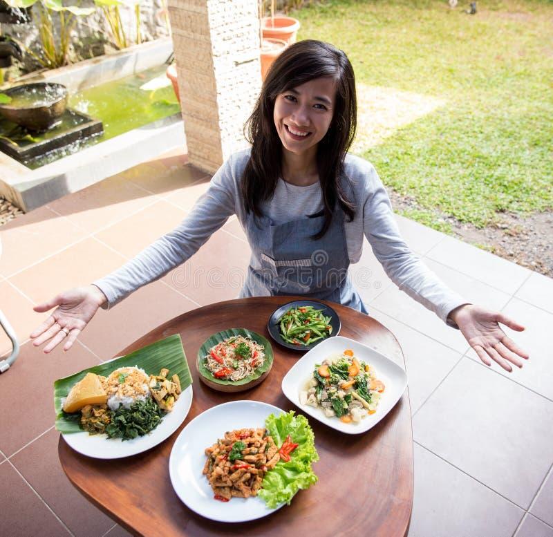 Donna che presenta vario alimento indonesiano fotografia stock libera da diritti