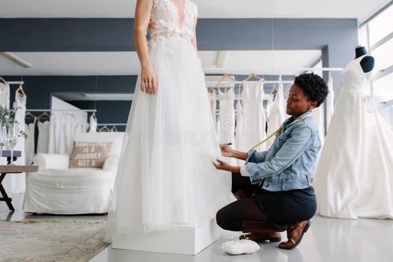 Donna che procede all'adeguamento all'abito di nozze nello studio del progettista fotografia stock