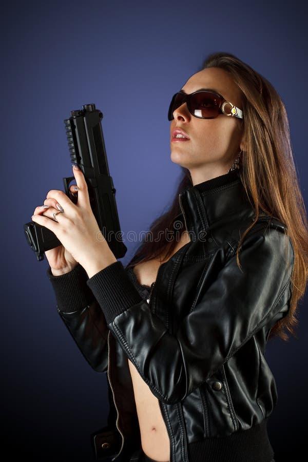 Donna che propone con la pistola fotografia stock libera da diritti