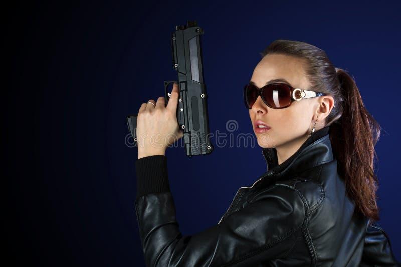 Donna che propone con la pistola immagine stock libera da diritti