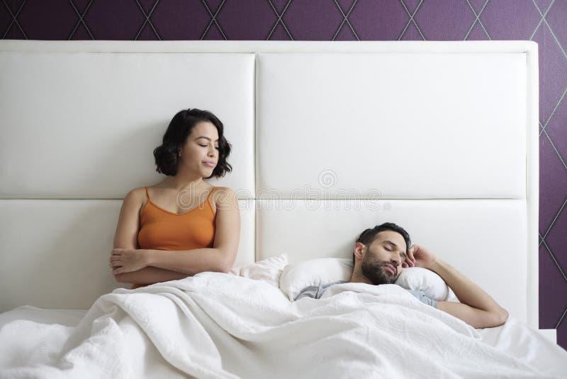 Donna che prova approccio sessuale con l'uomo in letto domestico immagine stock