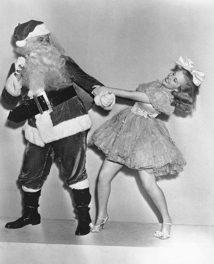 Donna che prova a ballare con Santa Claus (tutte le persone rappresentate non sono vivente più lungo e nessuna proprietà esiste G immagine stock libera da diritti