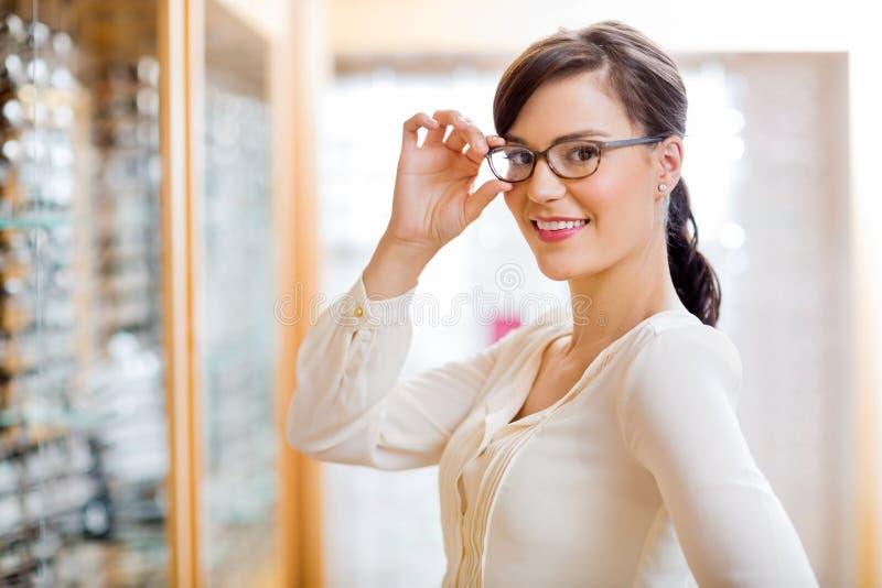 Donna che prova i nuovi vetri in ottico Store immagini stock libere da diritti