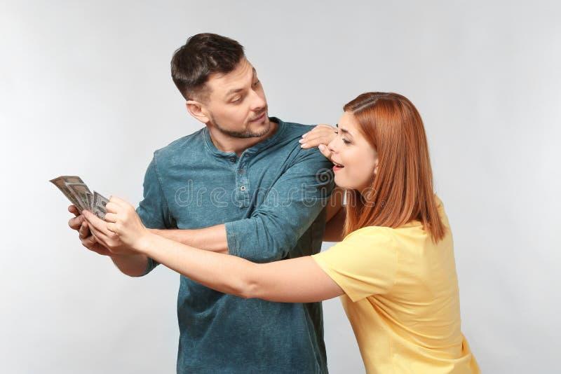 Donna che prova a prendere soldi dal suo marito immagini stock