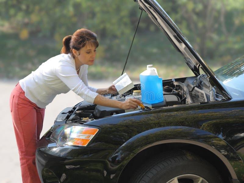 Donna che prova a riparare l'automobile fotografie stock libere da diritti