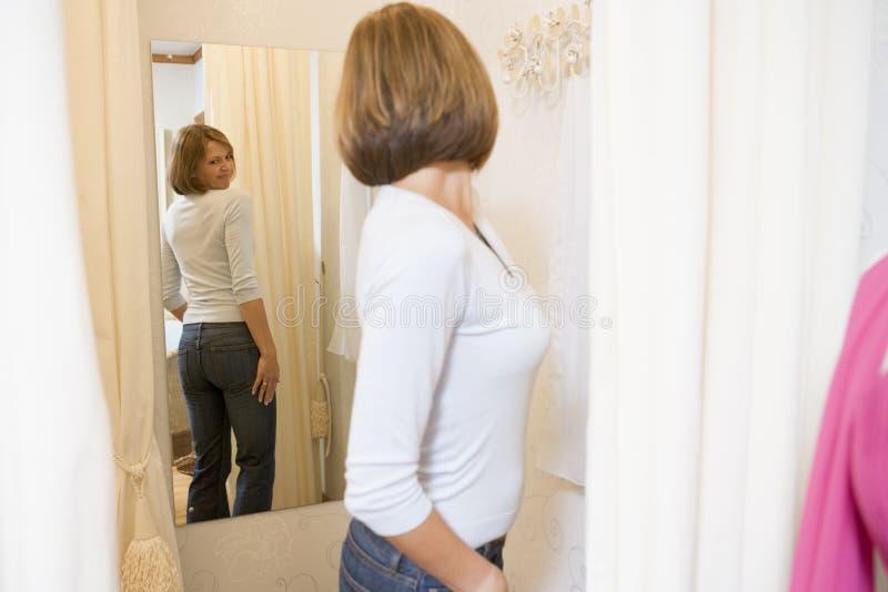 Donna che prova sui jeans e che aggrotta le sopracciglia immagine stock libera da diritti