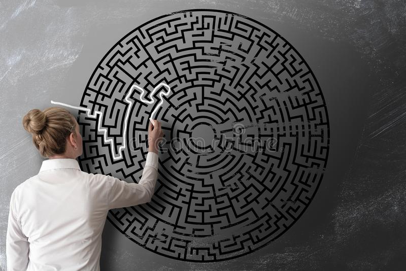 Donna che prova a trovare modo attraverso il disegno di gesso del labirinto sul concetto di sfida della lavagna immagine stock libera da diritti