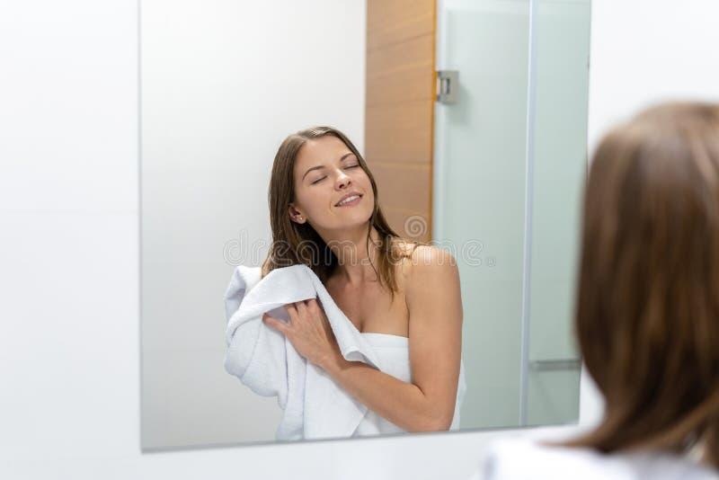 Donna che pulisce capelli bagnati con l'asciugamano in bagno immagine stock libera da diritti