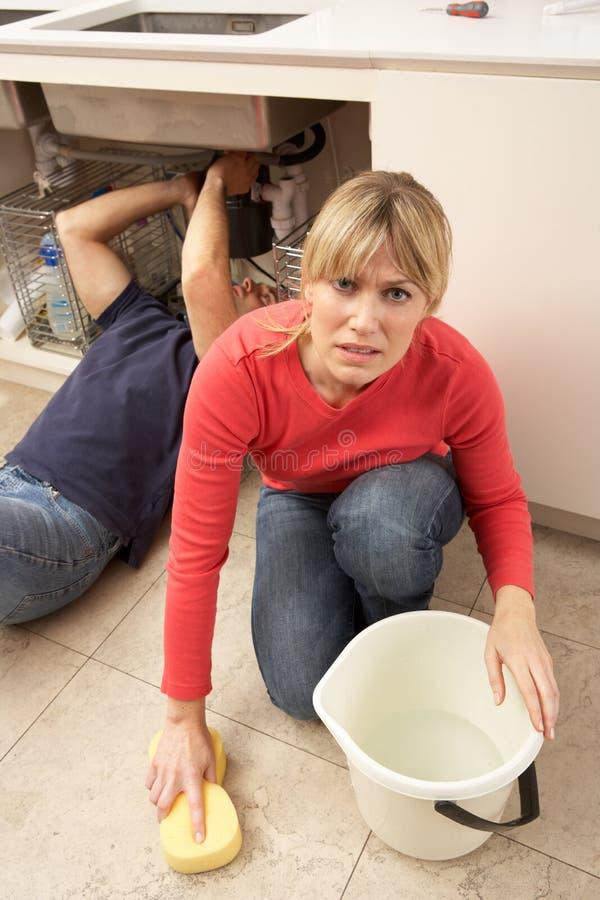 Donna che pulisce dispersore con lo straccio colante immagini stock