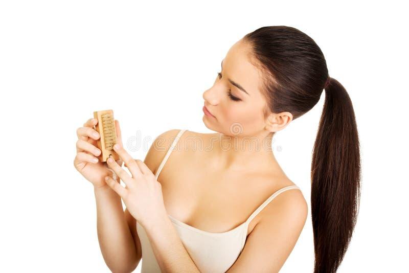 Donna che pulisce i suoi chiodi con la spazzola fotografia stock libera da diritti