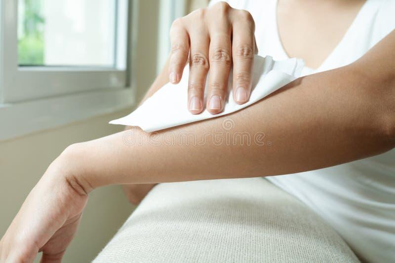 Donna che pulisce il suo braccio con la carta velina di tessuto molle bianca immagine stock