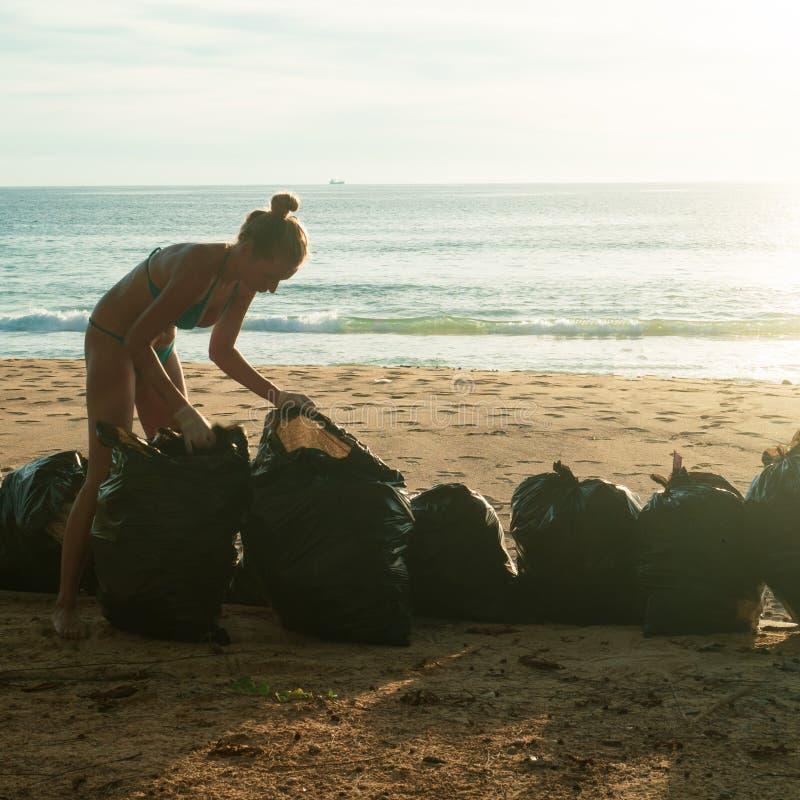 Donna che pulisce la spiaggia immagini stock
