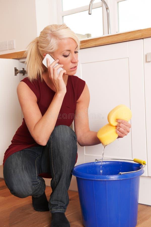 Donna che pulisce lavandino con lo straccio colante sul telefono all'idraulico di emergenza immagini stock libere da diritti