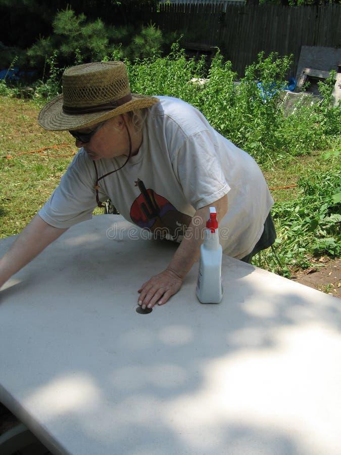 Donna che pulisce tabella esterna immagine stock libera da diritti